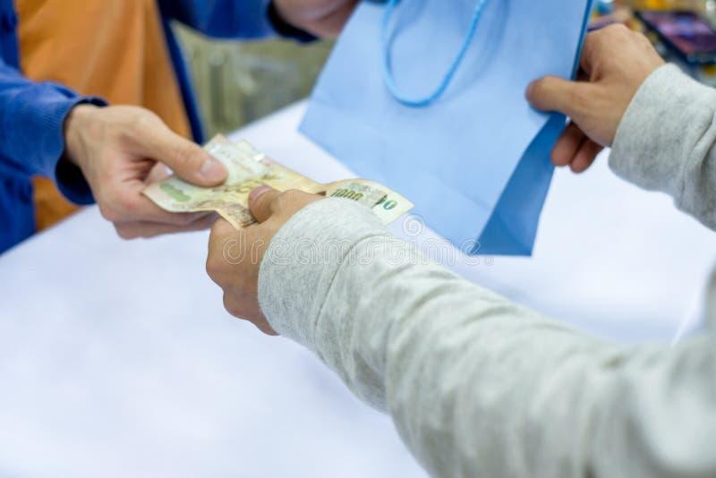 Wręcza dawać pieniądze i bierze papierową torbę od pięcioliniowego kasjera w sklepie zdjęcia royalty free