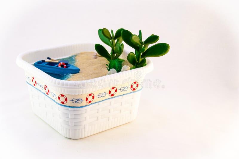 Wręcza gosposi, miniaturyzuje plażę z łodzią na piaskowatym brzeg, Błękitne wody z skorupami i roślinami zdjęcia royalty free