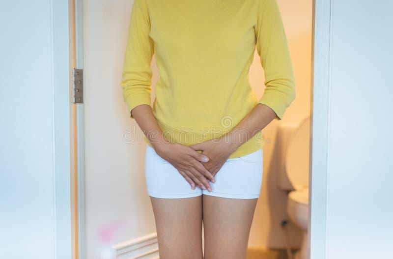 Wręcza kobiety trzyma jej crotch, Żeńska potrzeba siusiać zdjęcie stock