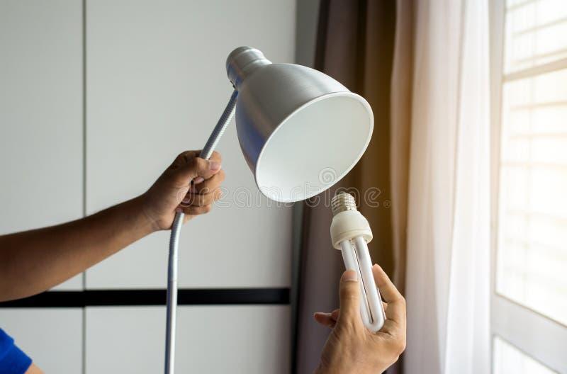 Wręcza mechanika odmienianie z nową DOWODZONĄ lampową żarówką, władzy oszczędzania pojęcie obraz stock