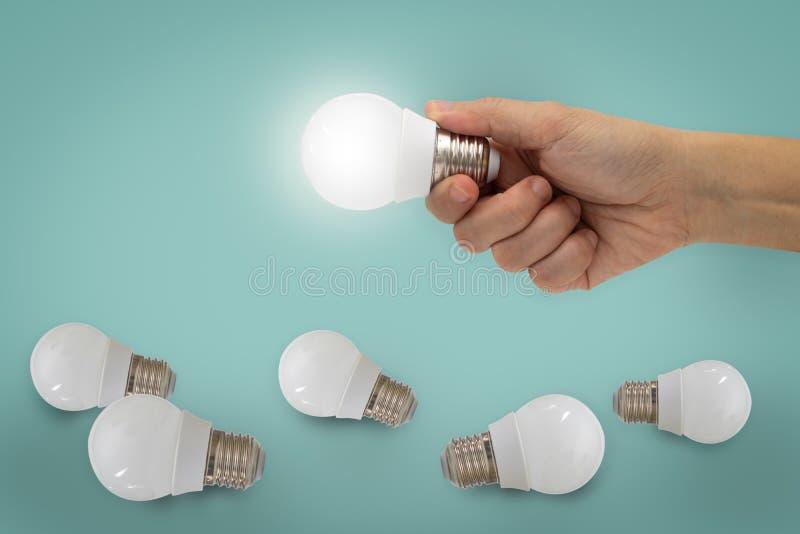 Wręcza mienie iluminującą żarówkę, pomysł, inspiraci pojęcie fotografia stock