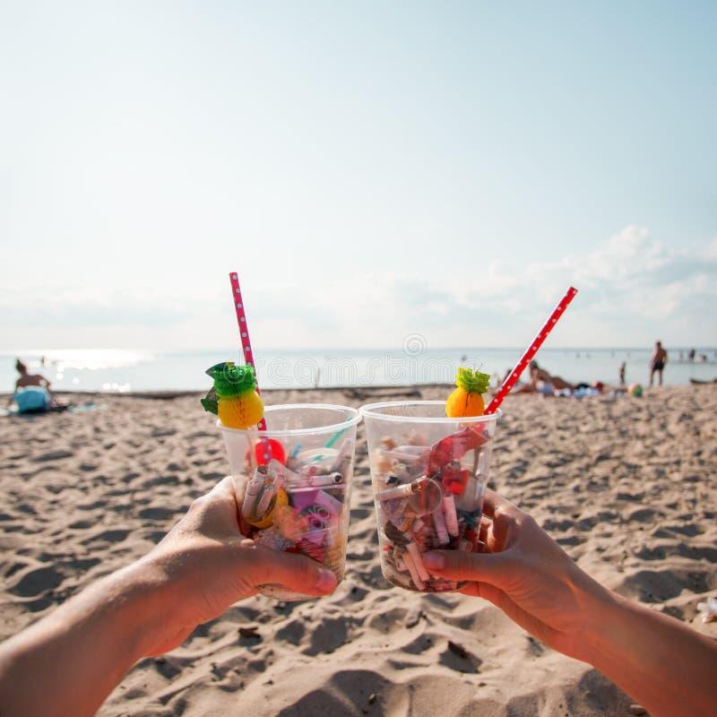 Wręcza mienie koktajl z śmieci na tle czysta plaża, ocean fale Plastikowy oceanu zanieczyszczenie, środowiskowy kryzys m?wi zdjęcie royalty free