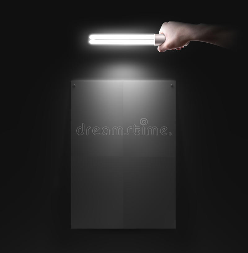 Wręcza mienie lampę blisko ściany z pustym plakatowym mockup zdjęcie royalty free