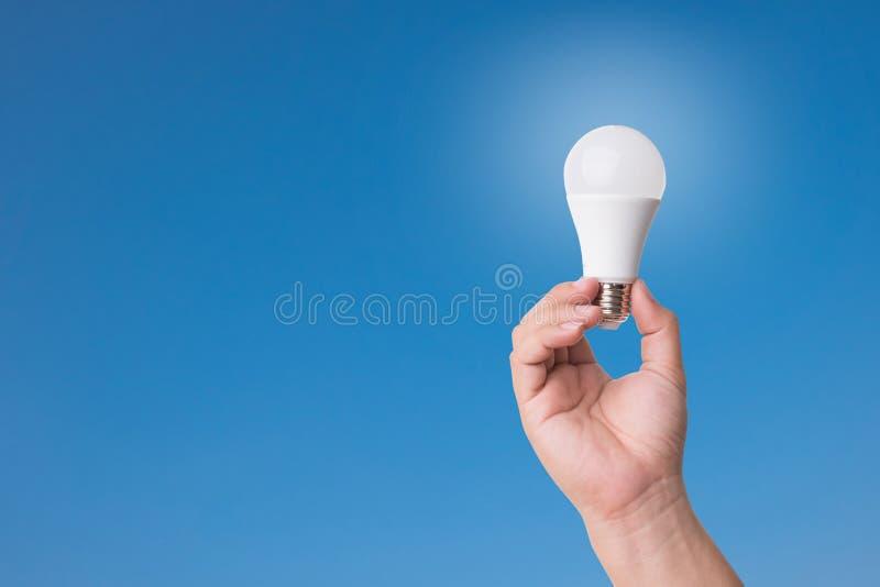 Wręcza mienie PROWADZĄCĄ żarówkę z oświetleniem na niebieskiego nieba tle zdjęcia stock