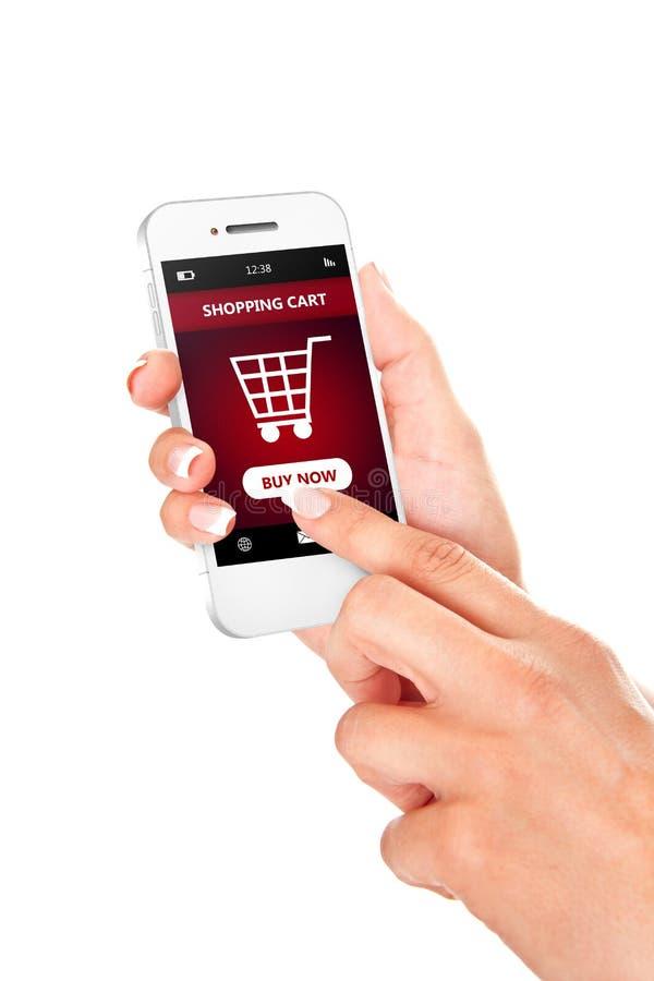 Wręcza mienie telefon komórkowego z wózek na zakupy odizolowywającym nad whit obraz stock