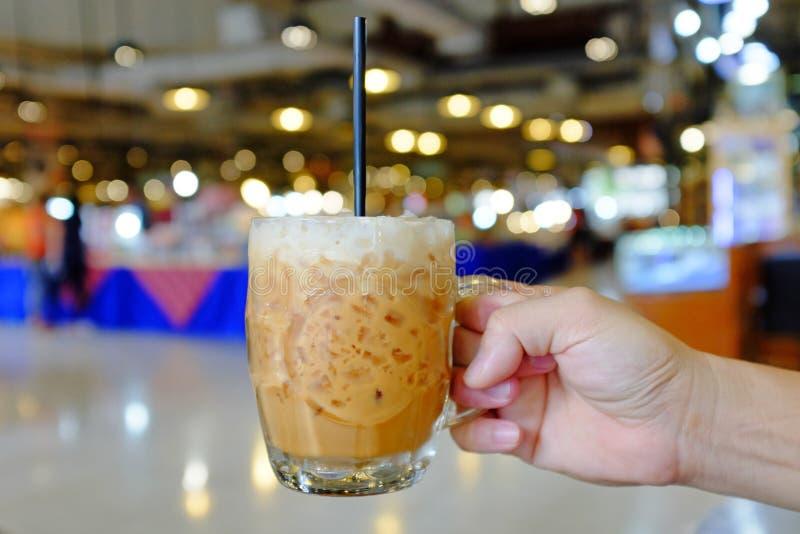 Wręcza mienie zamrażającą Tajlandzką dojną herbacianą szklaną filiżankę przeciw plama wizerunkowi domu towarowego tło zdjęcia royalty free