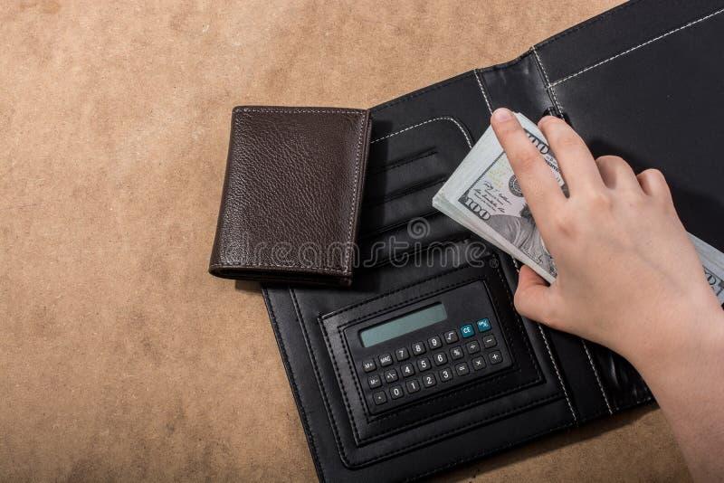 Wręcza mieniu Amerykańskich dolarowych banknoty kalkulatorem i portflem zdjęcie royalty free