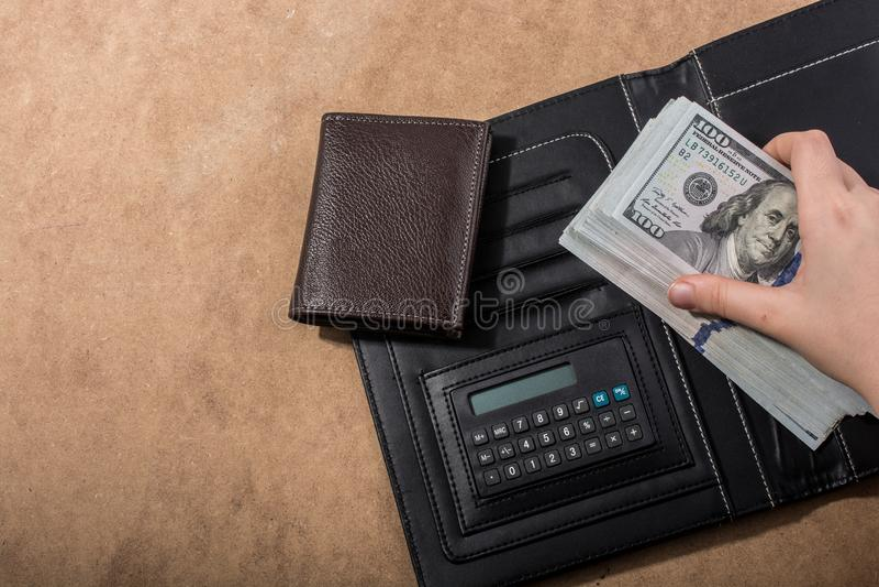 Wręcza mieniu Amerykańskich dolarowych banknoty kalkulatorem i portflem zdjęcie stock