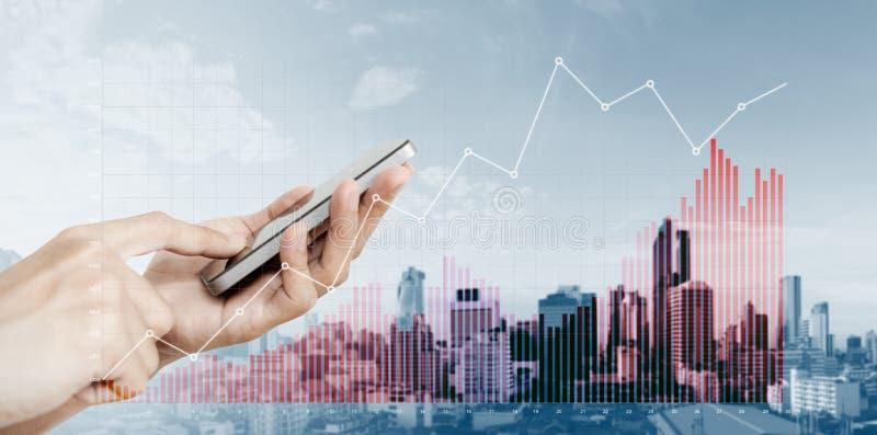 Wręcza mieniu mobilnego mądrze telefon z podnosić pieniężnych wykresy na miasta tle, zdjęcie stock