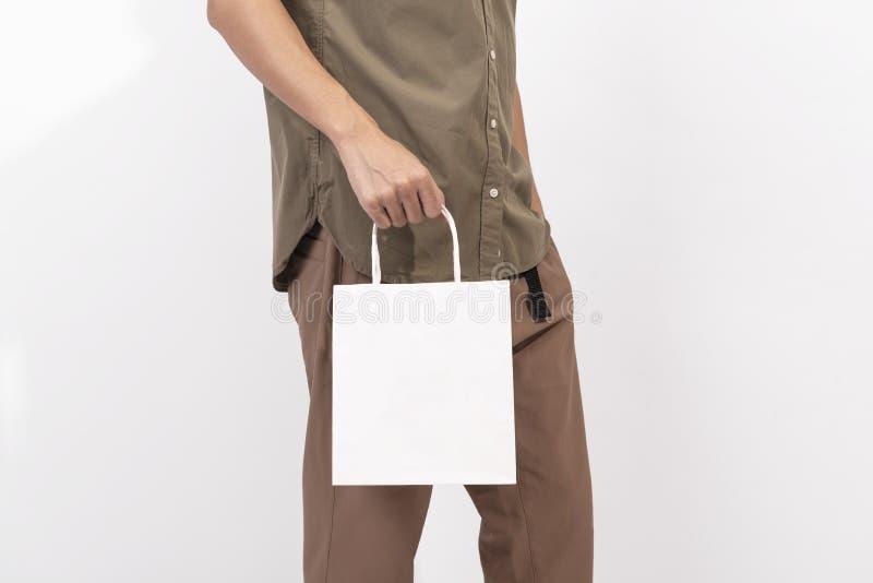 Wręcza mieniu pustą białej księgi torbę dla mockup szablonu reklamy i oznakować na szarym tle fotografia royalty free