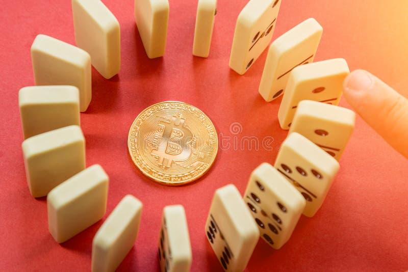 Wręcza niszczyć okręgu rząd domina z złotym bitcoin w centrum obrazy stock