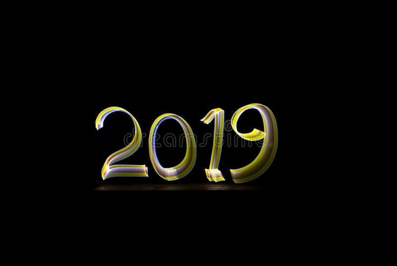 2019 - wręcza pisać z latarką odizolowywającą na czarnym tle Lekki obraz - Długa ujawnienie fotografia ilustracji