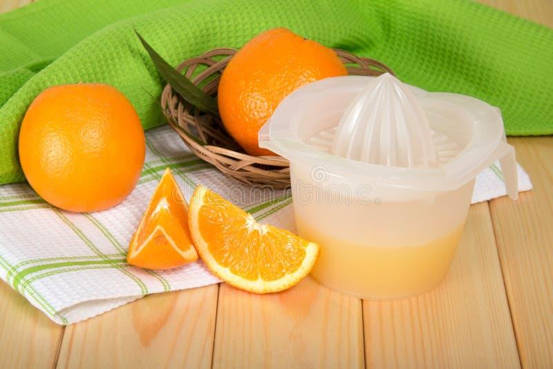 Wręcza prasy z gniosącym sokiem, pomarańcze w koszu obraz royalty free