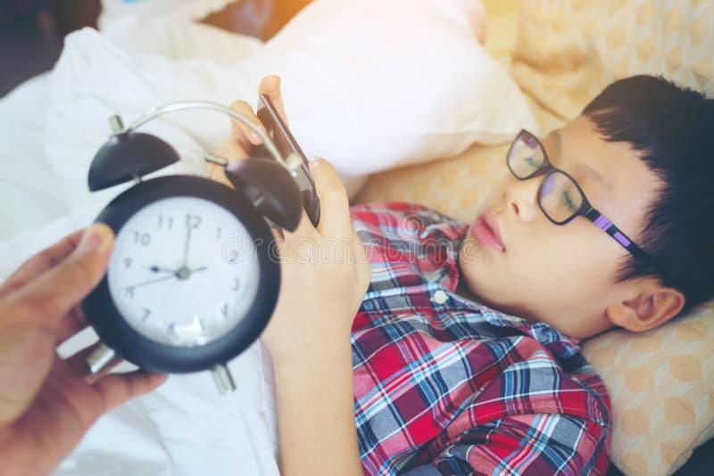 Wręcza przedstawienie out dla budzika na ranku, chłopiec bawić się w gama obraz royalty free