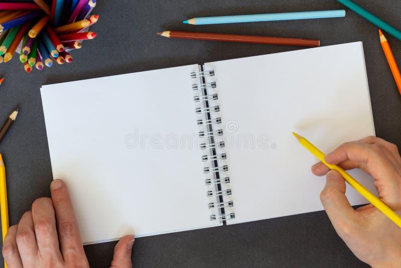 Wręcza rysunek, pustego papier i barwionych ołówki na ciemnego tła odgórnym widoku, fotografia royalty free
