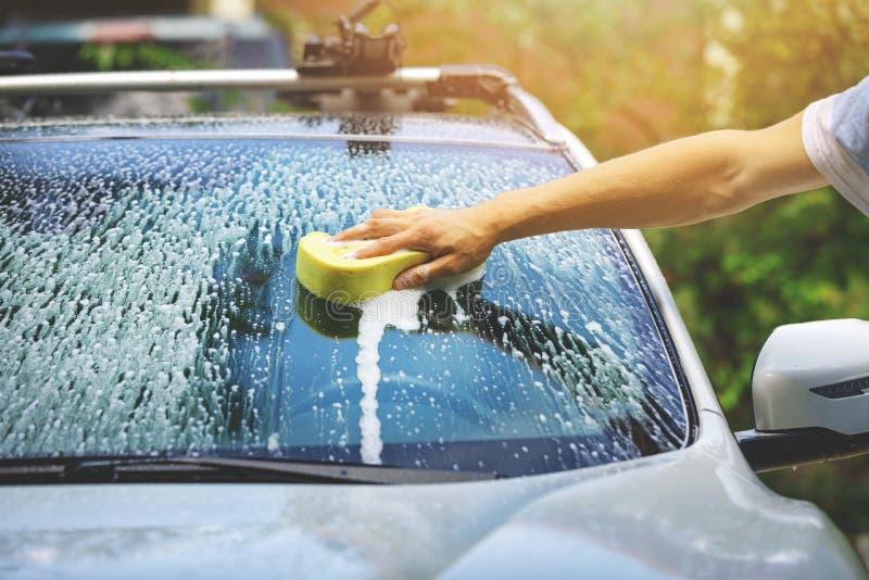 Wręcza samochodowego obmycie - myć przednią szybę z gąbką fotografia stock