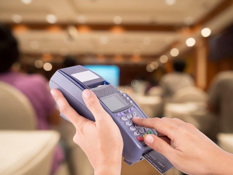 Wręcza Swiping Kredytową Karcianą maszynę z zamazanymi ludźmi obraz royalty free