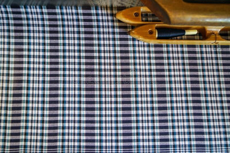 Wręcza tkaną bawełnianą tkaninę w cieniach farbujący błękitny i biały szkocka krata wzoru tło z drewnianym nicianym wahadłowem na zdjęcia royalty free