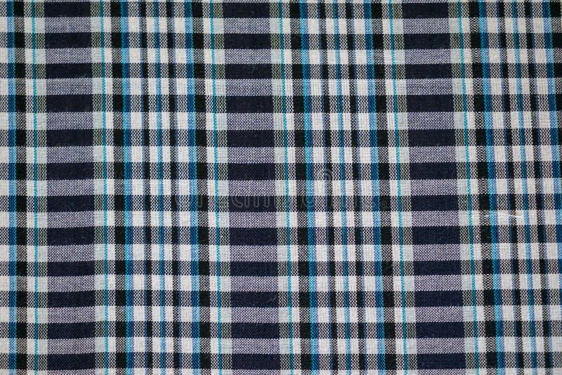 Wręcza tkaną tradycyjną bawełnianą tkaninę w cieniach farbujący błękitny i biały szkocka krata wzoru tło fotografia stock
