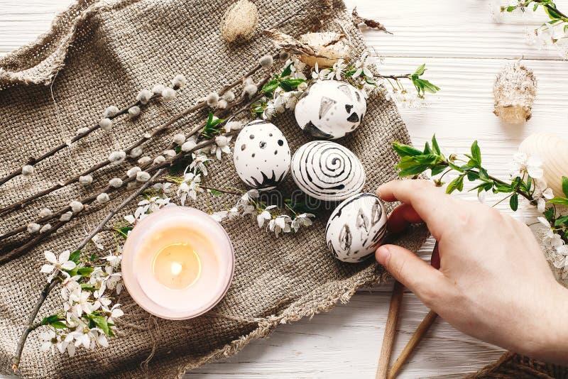Wręcza trzymać eleganckiego malującego Easter jajko przy nieociosanym drewnianym backgro zdjęcie royalty free