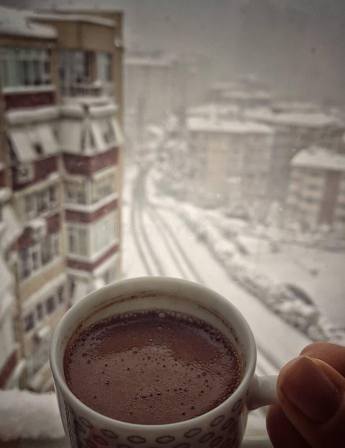 Wręcza trzymać filiżankę kawy przeciw miasto widokowi pod śniegiem w zimie zdjęcie stock