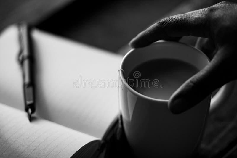 Wręcza trzymać kawowego kubek z czasopismem zdjęcia stock