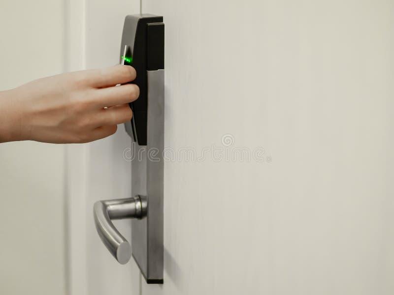 Wręcza trzymać kluczową kartę przed elektronicznym kędziorkiem otwarty biały drzwiowy pokój w hotelu obraz royalty free