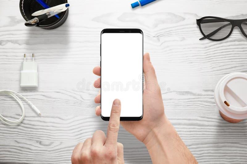 Wręcza trzymać nowożytnego mądrze telefon z bielu ekranem dla mockup, app lub wyczulonej strony internetowej promoci, fotografia stock