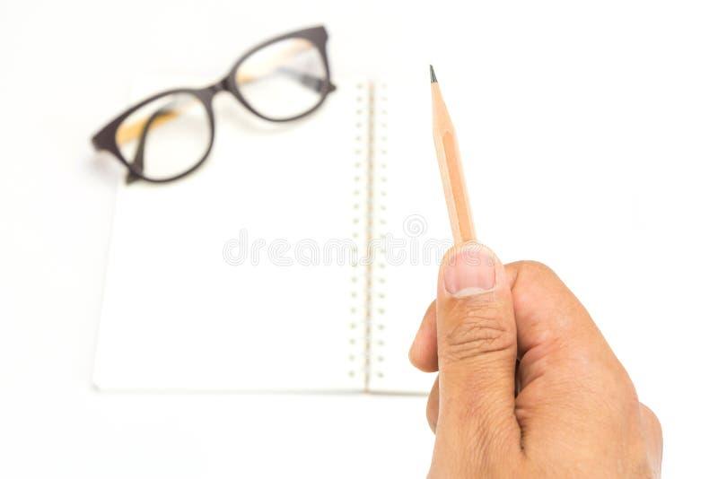 Wręcza trzymać ołówek z notatnikiem i przygląda się szkła obraz stock