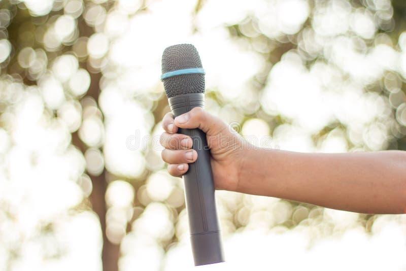 wręcza trzymać pojedynczego mikrofon przeciw colourful tłu, si zdjęcia royalty free