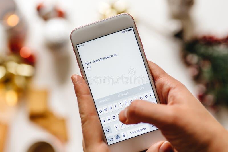Wręcza trzymać smartphone i pisać nowy rok postanowieniach, półdupki obrazy royalty free