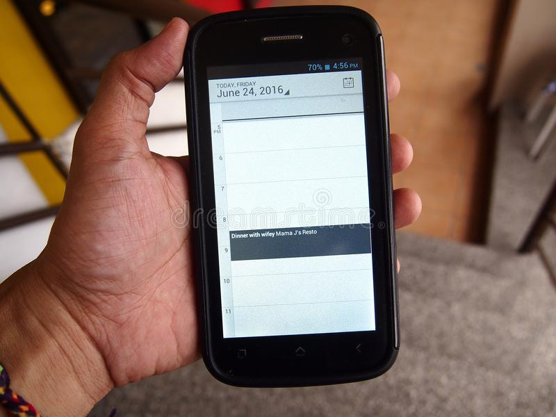 Wręcza trzymać smartphone z kalendarzowym przypomnieniem zdjęcia stock