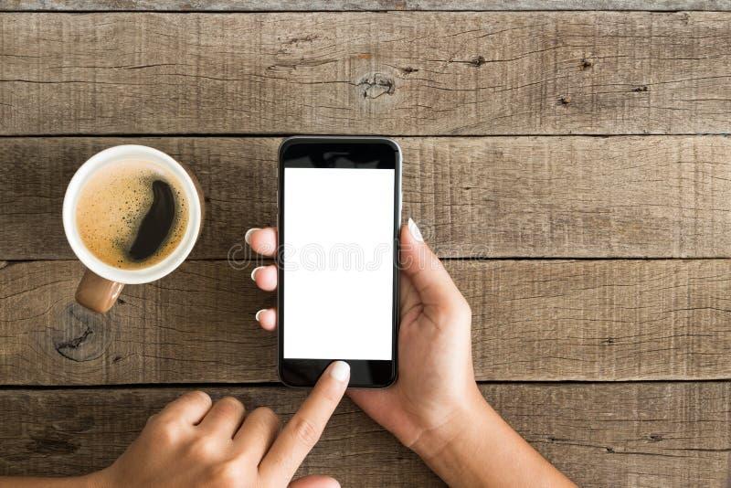 Wręcza używać telefonu bielu ekran na odgórnym widoku zdjęcia stock