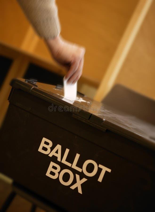 Wręcza umieszczać głosowanie w tajnego głosowania pudełku w lokalu wyborczym fotografia stock