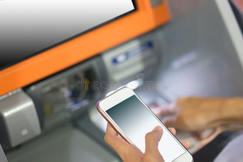 Wręcza wkładać kredytową kartę w atm trzyma mądrze telefon zdjęcia royalty free