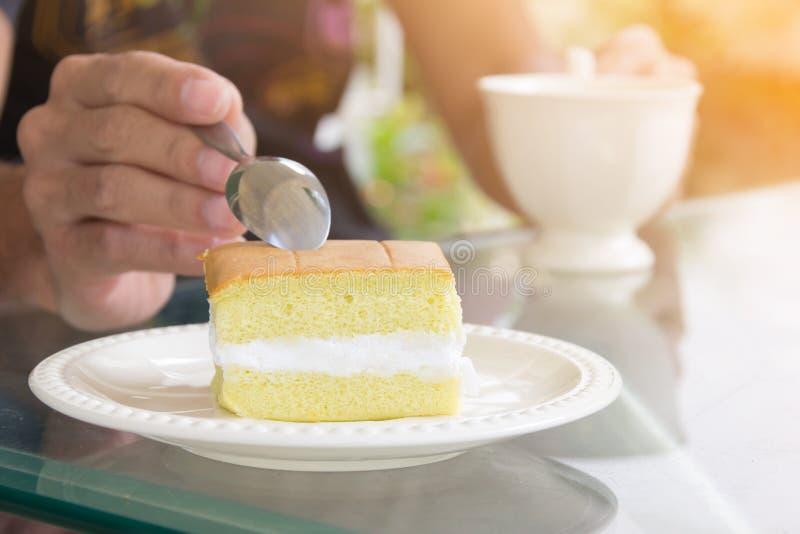 Wręcza wp8lywy szyfonowego tort małą łyżką i trzymać czarną filiżankę zdjęcia stock