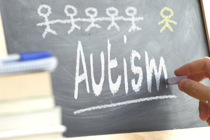 Wręcza writing na blackboard w klasie z słowem autyzm pisać dalej zdjęcie royalty free
