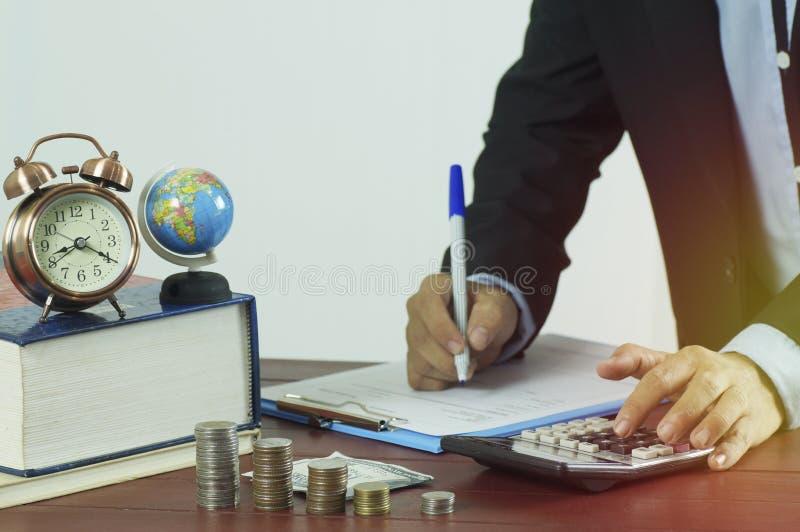 wręcza writing na papierze i naciska kalkulatora z stosem pieniądze moneta, pojęcie w finanse fotografia stock