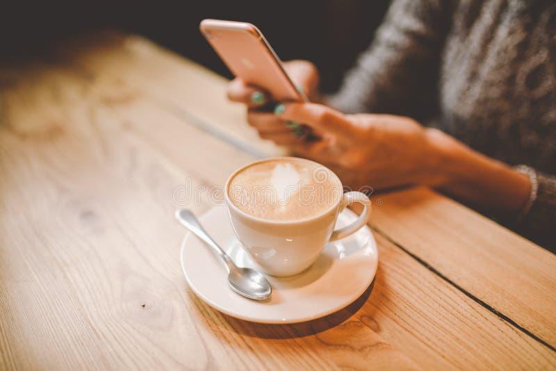 Wręcza zakończenie młodej dziewczyny piękni uses, typ teksty na telefonie komórkowym i napoje, przy drewnianym stołem blisko okno obrazy stock