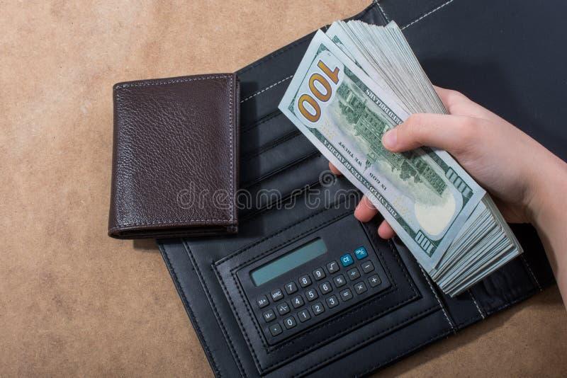 Wr?cza mieniu Ameryka?skich dolarowych banknoty kalkulatorem i portflem zdjęcia royalty free