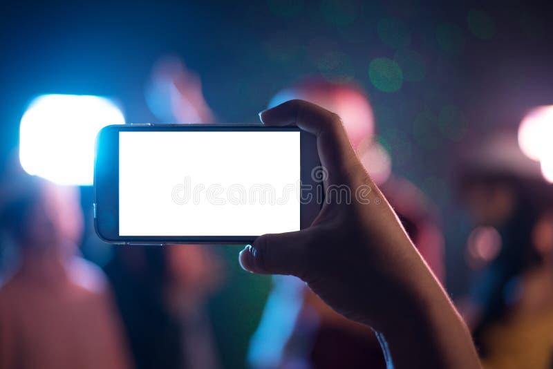 Wr?cza trzyma? m?drze telefon z pustym bielu ekranem Fotografia strzelaj?cy rozmyty koncert, przyj?cie i m?drze obraz royalty free