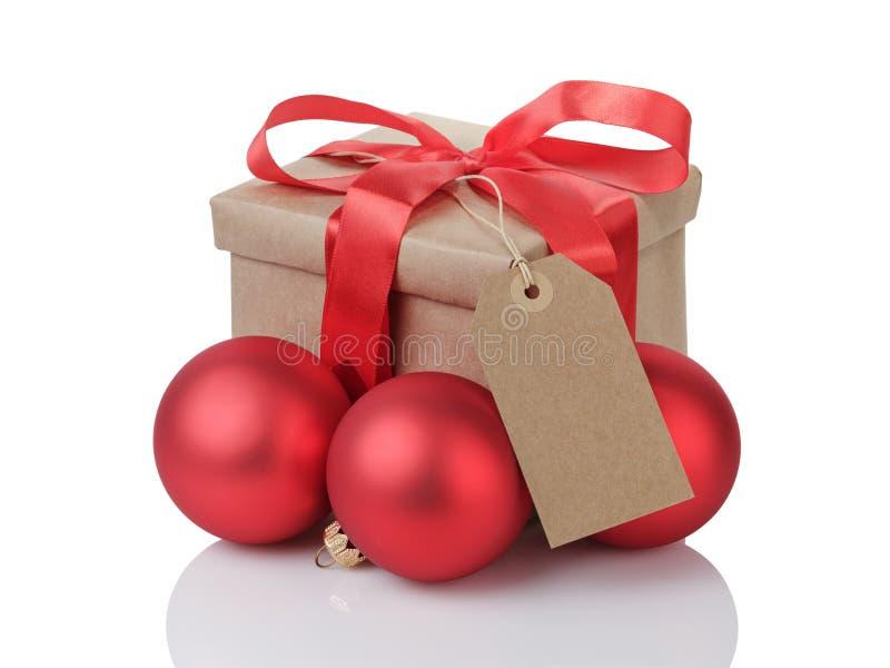 Wraped gåvaask med den röda pilbågen, julbollar och etiketten royaltyfri fotografi