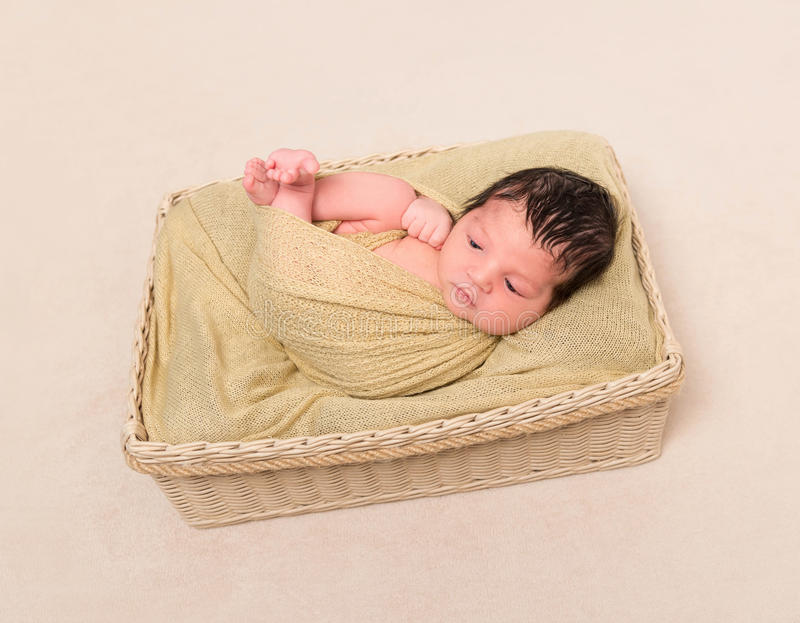 Wrapped black-haired baby basket, topview stock photography