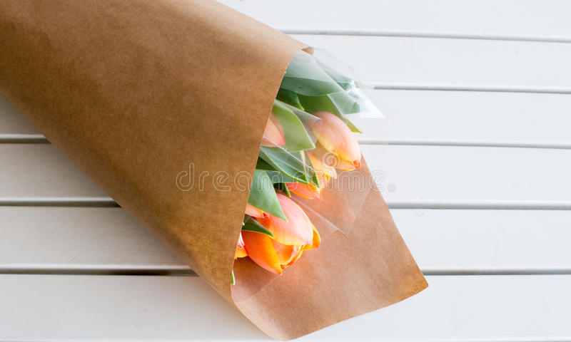 Wrapped bouquet of orange tulips on table stock image