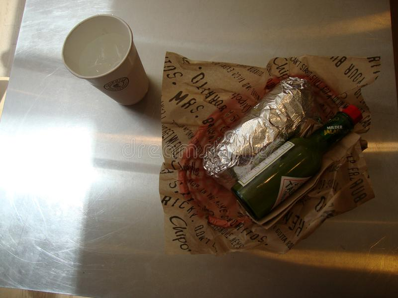 Wrapped Burrito with drink and green tabasco at Chipotle stock photography