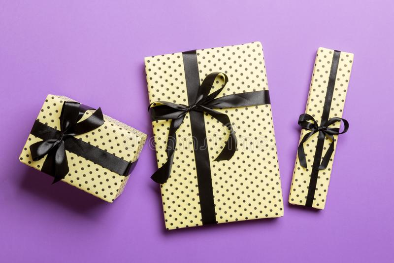 Wrapped Christmas or other holiday handmade present in paper with Black ribbon on purple background. Present box, decoration of stock photos