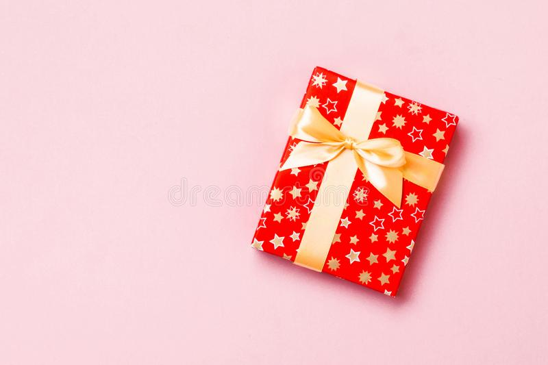 Wrapped Christmas or other holiday handmade present in paper with Gold ribbon on pink background. Present box, decoration of gift stock photos