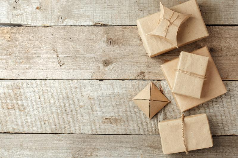 Wrapped christmas presents in paper craft package on vintage wooden background, copy space. stylish gifts, seasonal greetings, stock photos