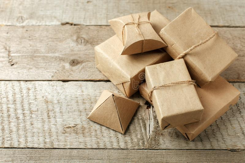 Wrapped christmas presents in paper craft package on vintage wooden background, copy space. stylish gifts, seasonal greetings,. Concept of holiday preparation royalty free stock images