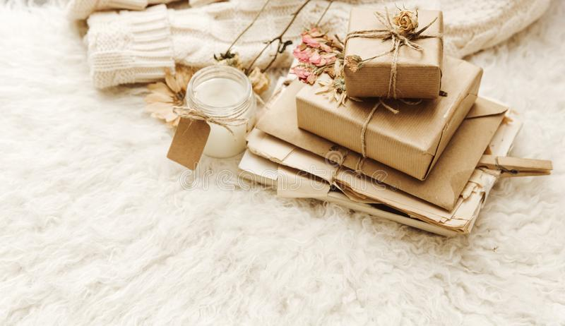 Wrapped craft gift boxes with dry flowers over fur background. royalty free stock photography